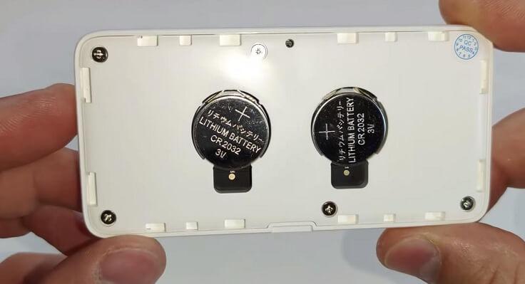 С тыльной стороны снизу под крышкой находятся две батарейки cr 2032